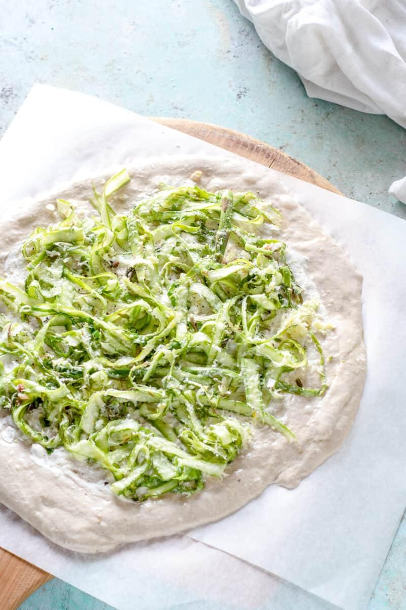 Shaved asparagus on pizza dough