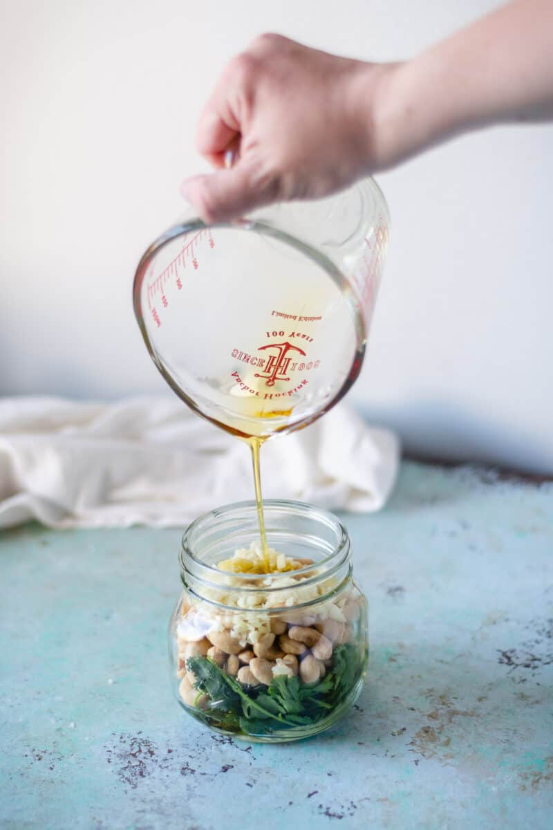Olive oil being poured into a jar with cashews and cilantro