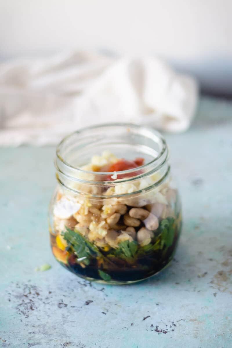 Jar with sriracha, garlic, cashews, lime juice