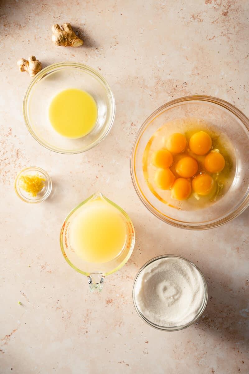 Ginger juice, eggs, sugar, lemon juice, and lemon zest in glass prep bowls