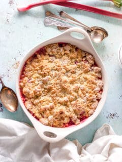 Rhubarb Crumble in a baking dish with two stalks of rhubarb alongside