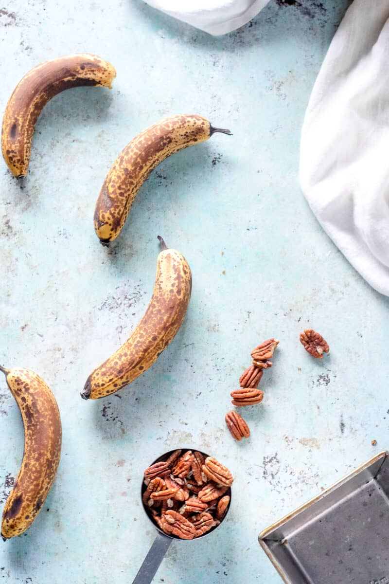 Ripe Bananas, pecans, and an empty loaf pan